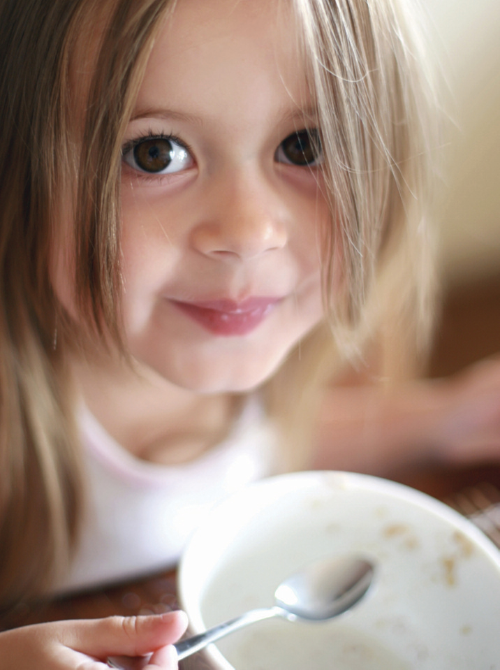 child finishing eating a bowl of oatmeal