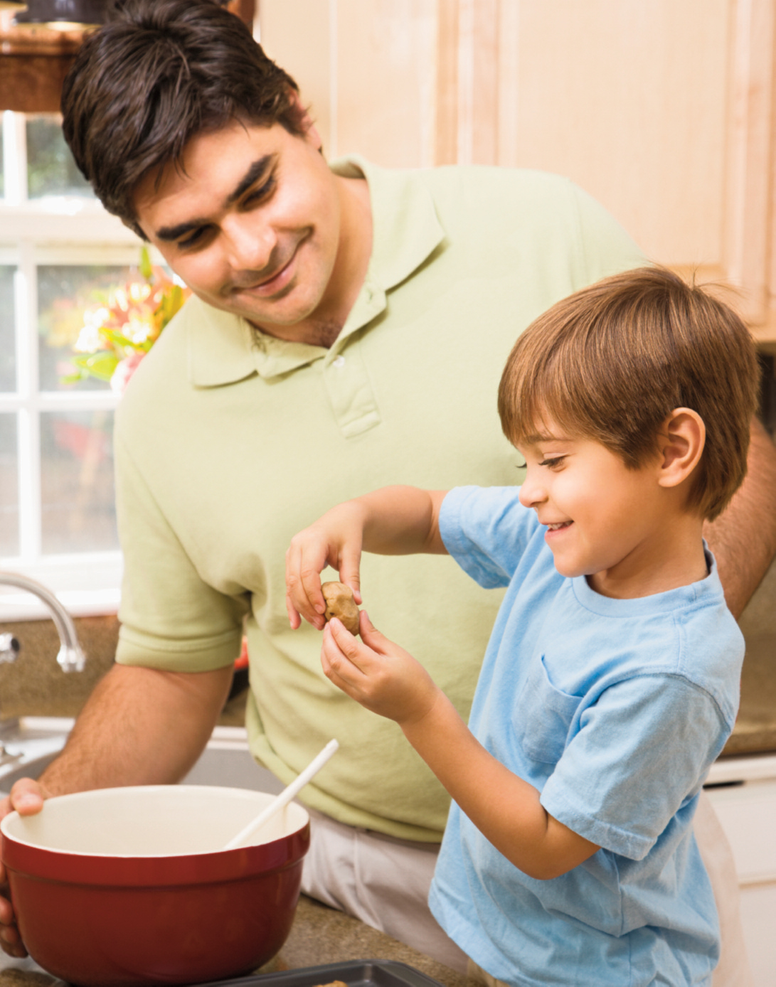 father holds mixing bowl while son shapes cookie dough