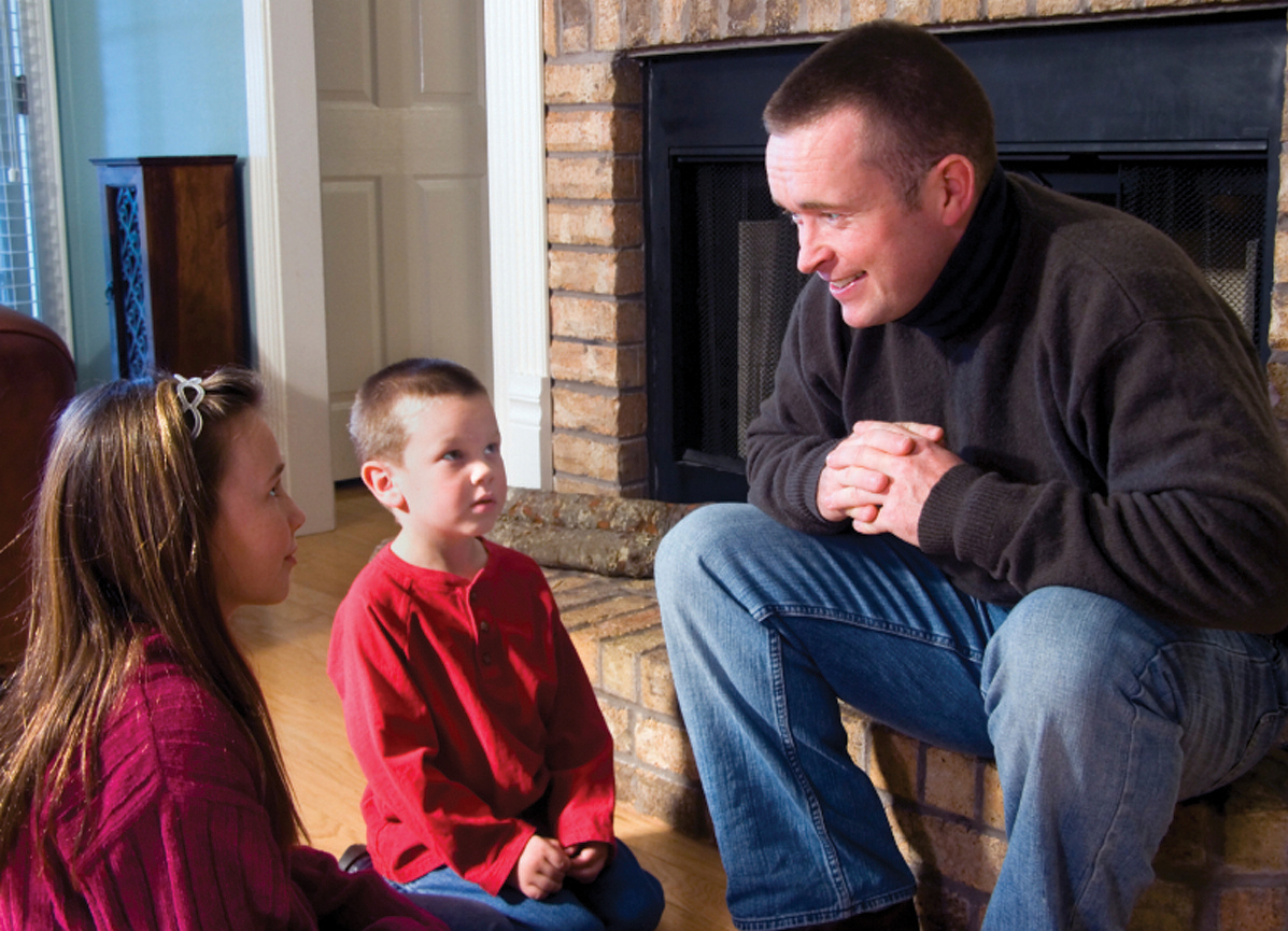 father sitting on hearth looking at children sitting on the floor