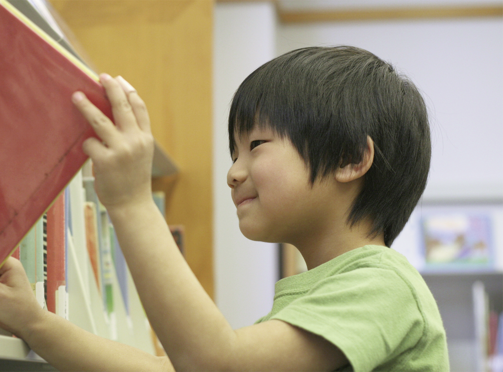 child taking a book off a library shelf