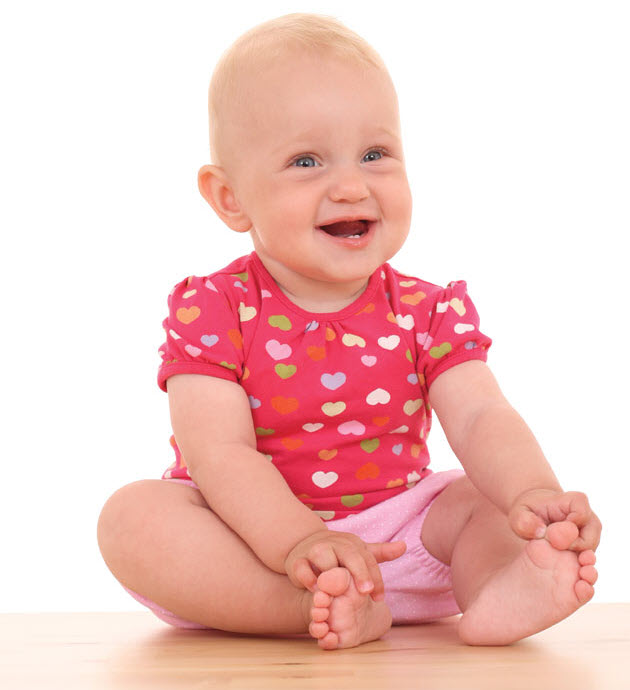 Baby smiling holding toes with mouth open