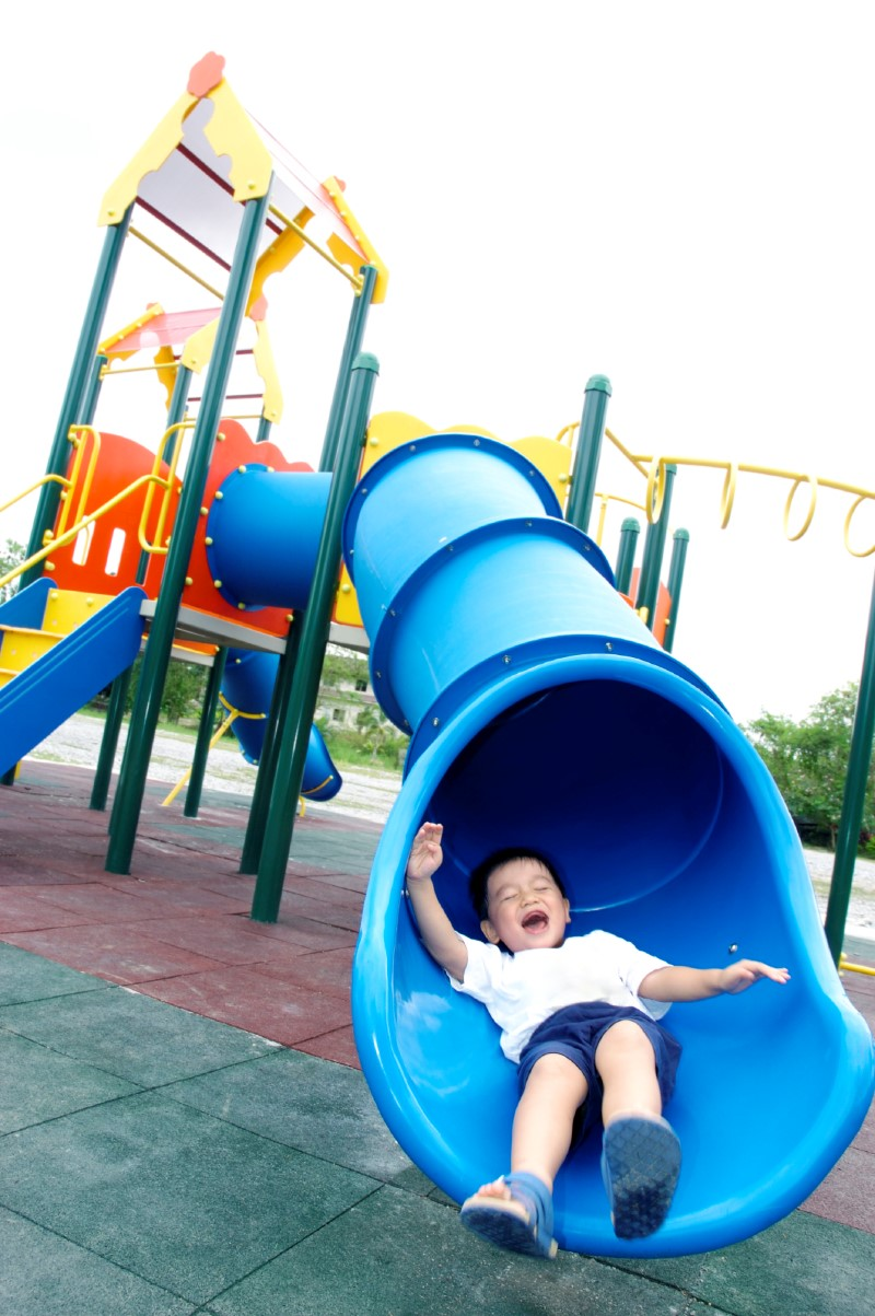 A young boy coming out of a slide in a playground.